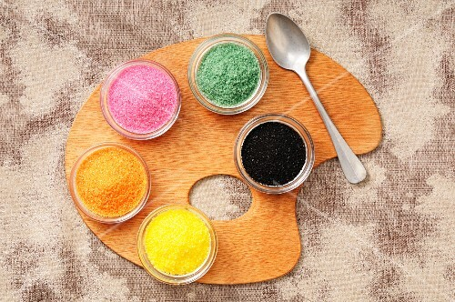 Coloured sugar in small pots on a palette