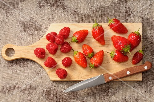 Fresh strawberries and raspberries on a chopping board with a knife