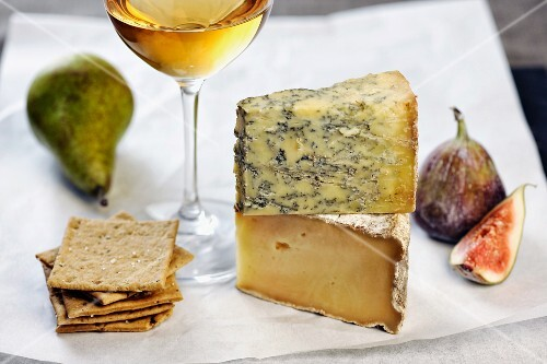 Assorted types of cheese with figs, a pear, crackers and a glass of white wine