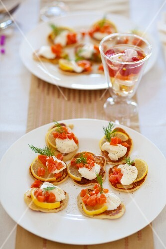 Mini pancakes with lemon slices, sour cream, smoked salmon and fennel tops
