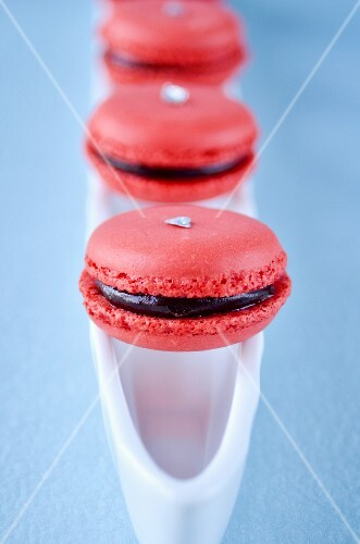 Raspberry macaroons with chocolate filling on a white dish with a blue background