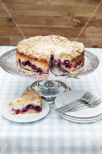 Crumble-topped quark cake with blackberries, one slice cut