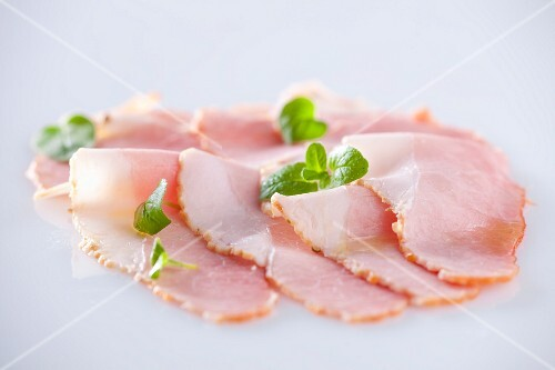 Slices of ham with oregano leaves