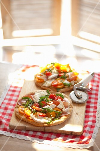 Pizzas with rocket, prosciutto, goat's cheese and tomatoes