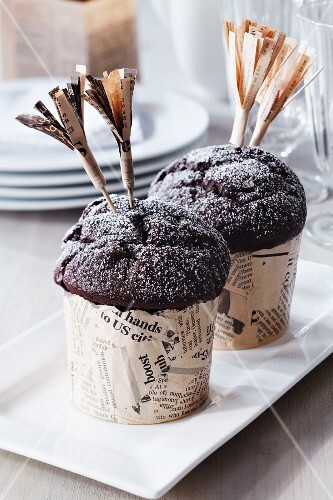 Muffins in paper cases covered with newspaper and embellished with cocktail stick decorations