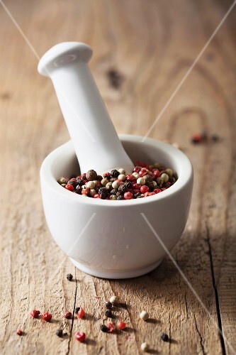 Colorful peppercorns in a mortar on a wooden background