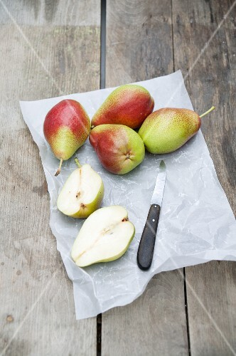 Several pears, whole and halved, on grease-proof paper with a knife