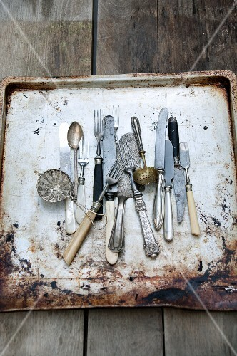 Antique cutlery on a rusty baking tray