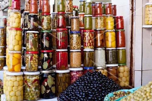 Lots of jars of assorted preserved food and mounds of olives in a shop