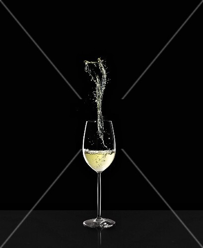 A glass of white wine with a splash