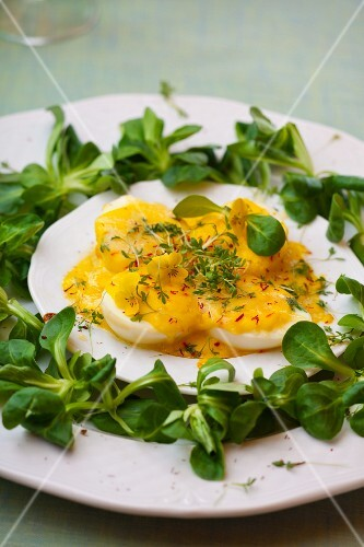 Halved boiled eggs with mayonnaise and cheese sauce, garnished with lamb's lettuce, saffron and cress