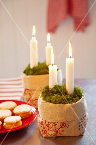 Candles in a linen sack with moss, a plate of biscuits to one side