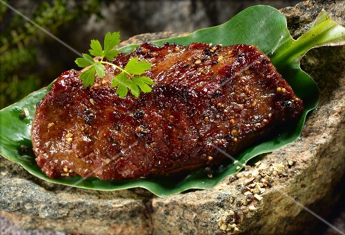 Grilled rump steak on a banana leaf