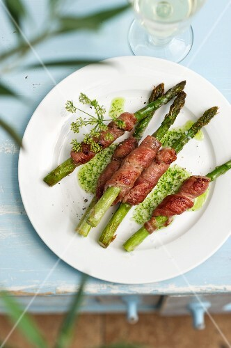 Grilled green asparagus wrapped in bacon with a herb sauce