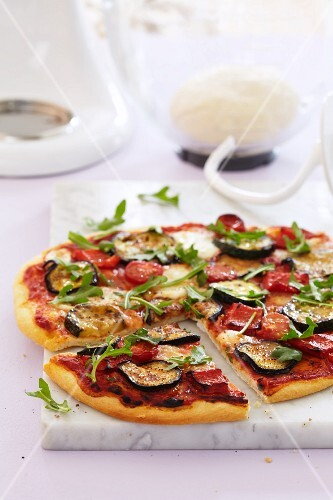Vegetable pizza topped with peppers, courgette and rocket