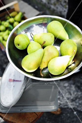 Green pears on weighing scales at the market