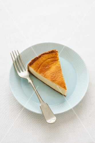 A slice of baked cheesecake on a plate against a white background