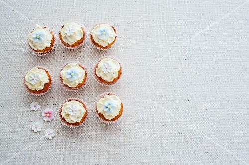 Eight cupcakes decorated with sugar flowers (view from above)