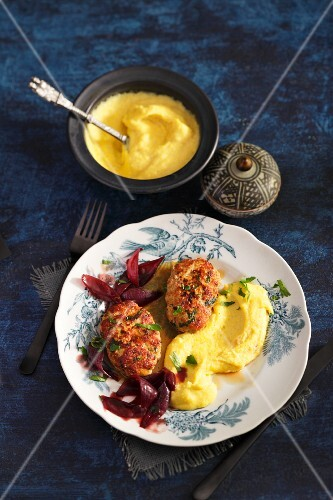 Kalbsbutterschnitzel (minced veal patties fried in butter then braised) with onions cooked in red wine, and polenta (Viennese cuisine)