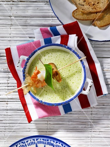 Courgette soup with a prawn skewer