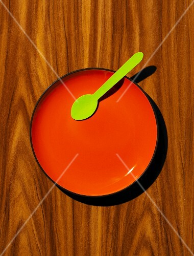 Red plate, with green wooden spoon on a wood effect background