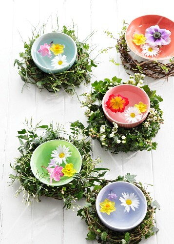 Spring flowers floating in colourful bowls of water surrounded by wreaths