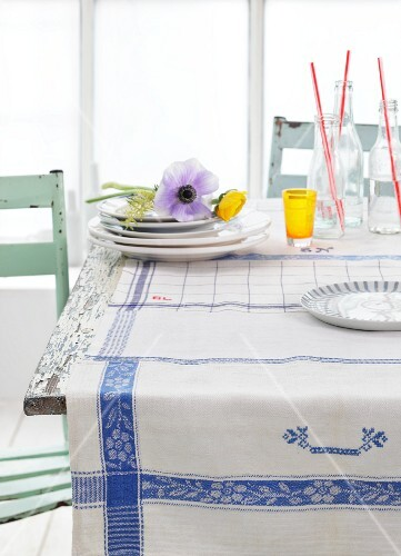 Blue and white tea towels used as tablecloth, anemones on stacked plates and bottles on rustic kitchen table