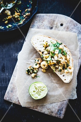 A slice of bread topped with prawns, miso and limes
