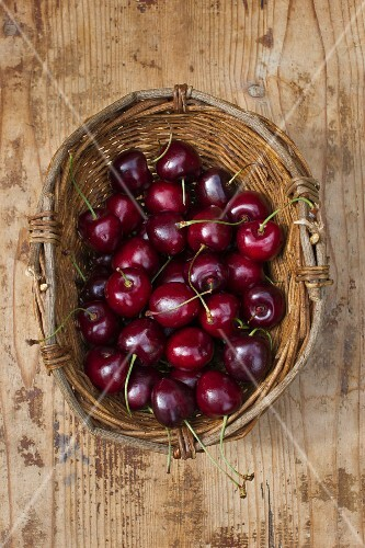 A basket of cherries on a wooden surface (view from above)