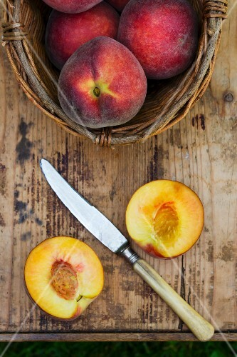 Peach with a basket and a knife on a wooden table