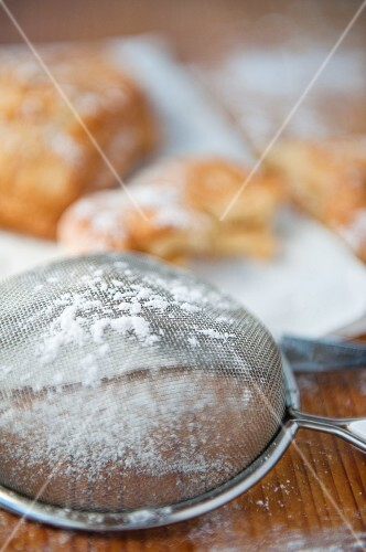 A sieve with icing sugar, baked pastries in the background