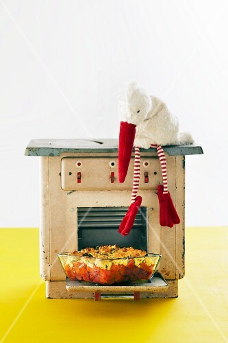 Tomato stew in front of a toy oven