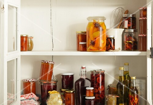 Preserved and pickled fruits in an open storage cupboard