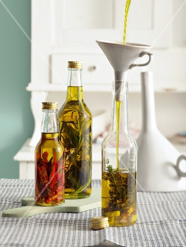 Oils flavoured with herbs, garlic and chilli being made