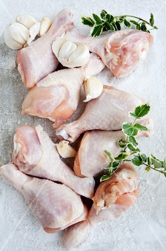 Raw chicken drumsticks with garlic (view from above)