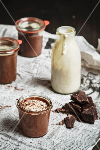 Three jars of chocolate dessert and a glass of vanilla sauce on newspaper