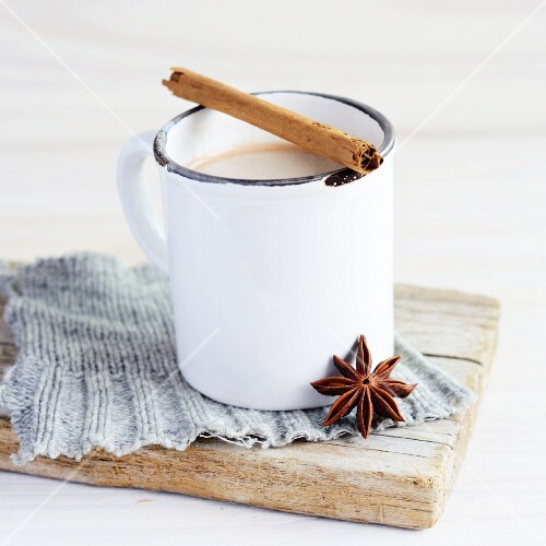 A white enamel mug of tea, with a cinnamon stick across the top and a star anise resting against the mug; the ensemble is on a piece of grey knitting on a weathered board