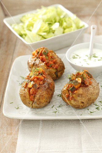 Baked potatoes with minced meat and vegetable filling and a yoghurt dip