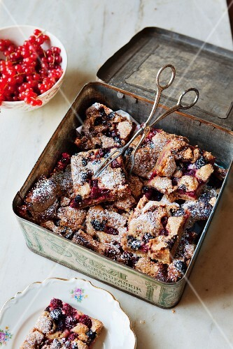 Cinnamon cake with mixed berries, slices in a tin box and on a plate
