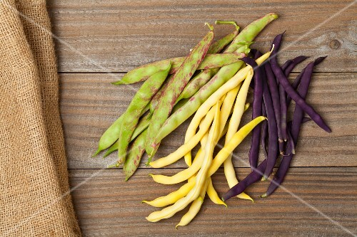 Wax beans, scarlet runner beans and blue French beans on a wooden table