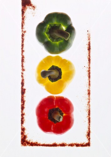 Three peppers, backlit, with a frame made from ground paprika
