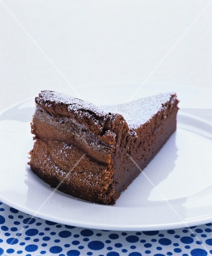 A slice of chocolate cake with icing sugar