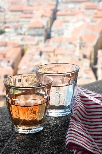 A glass of wine and a glass of water on a stone wall above the city of Nice