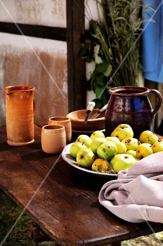 A still life featuring clay pots and a bowl of apples on a wooden table