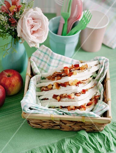 Tramezzini (Italian crustless sandwich triangles) with apple and cream cheese in a bread basket