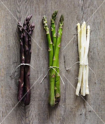 Purple, green and white asparagus stalks on a wooden surface