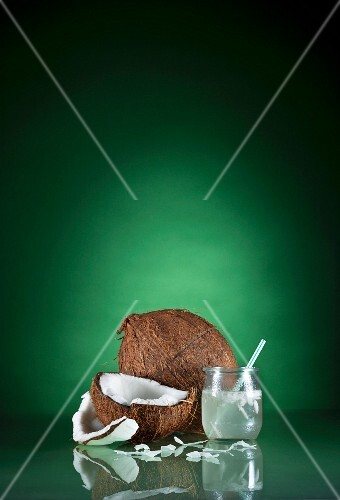 A Glass of Coconut Water with a Straw and Fresh Coconut