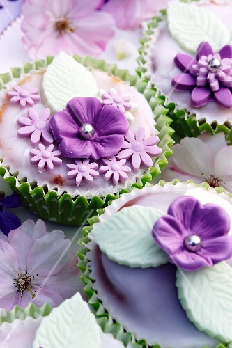 Muffins decorated with glacé icing and purple sugar flowers