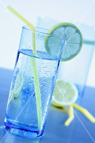 Blue glasses with water, lemons slices and yellow straws