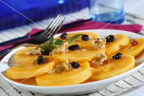 Persimmon kaki (sharon fruit) slices with raisins, walnuts and syrup